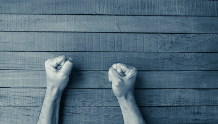 76564386 - man fists on a wooden table